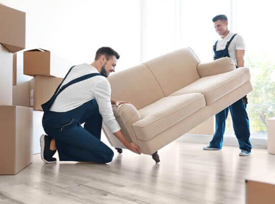 Männer beim Entladen von Möbeln aus einem Lieferwagen