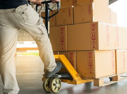 trabajador cargando palets para su transporte