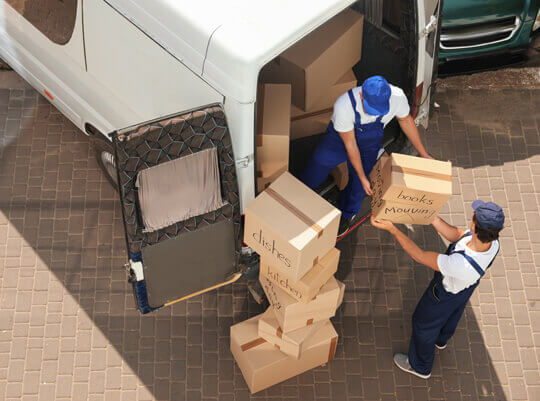 removal men load cardboard boxes into van shipping to France