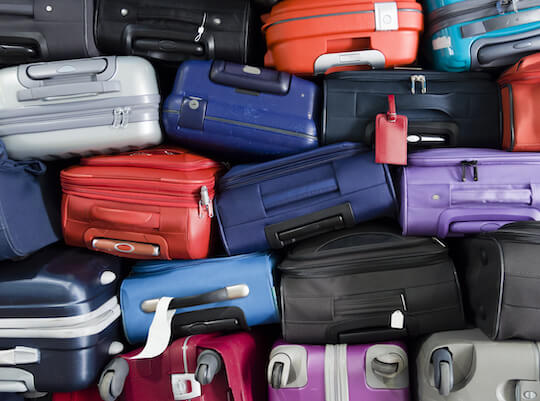 suitcases and luggage in a pile waiting for delivery