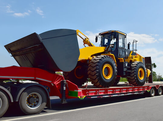 tractor on a flatbed being transported